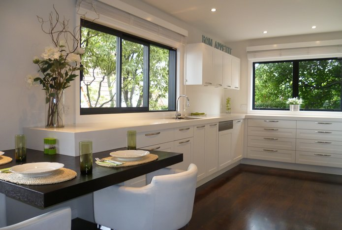 White kitchen design by Nicola Manning Design with split level dark bench top for dining
