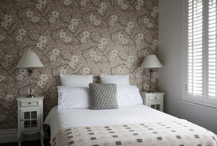 Bedroom design from Nicola Manning Design with light bedding and floral wallpaper, neutral colours