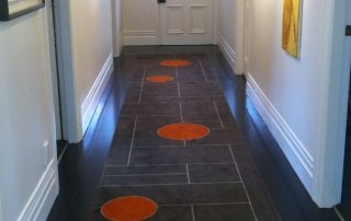 Nicola Manning Design custom rug in orange and grey with stained glass window