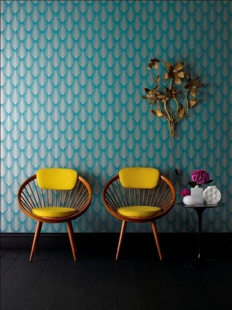 Setting with detailed blue patterned wallpaper, walnut and yellow retro armchairs and brass floral art with side tables and accesories
